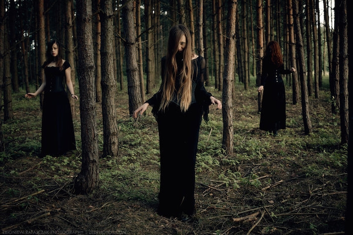 coven de sorcière vêtues en longues robes noires, look sorcière sans maquillage, sorcières dans la forêt, cadre naturel