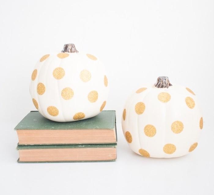 citrouille repeinte en blanc avec des pois dorés pailletées sur une pile de livres ancienne, idee deco halloween simple