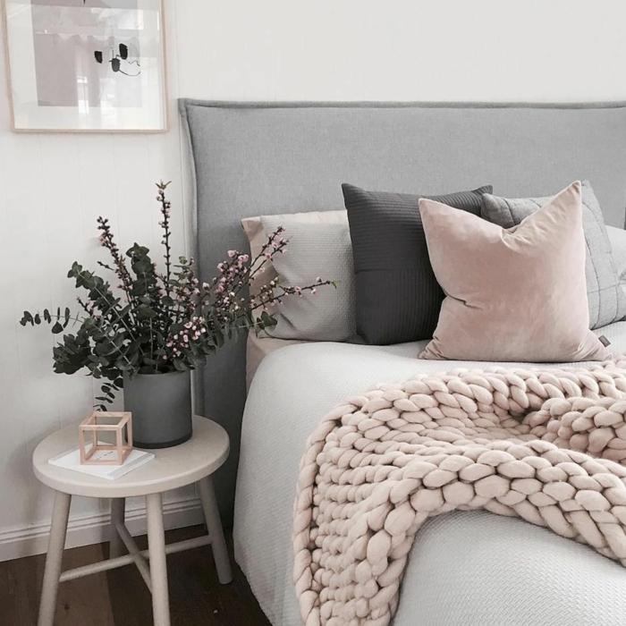 plaid rose pastel grosse maille, petit tabouret blanc, pot de fleur gris, coussins roses et gris, cadre peinture
