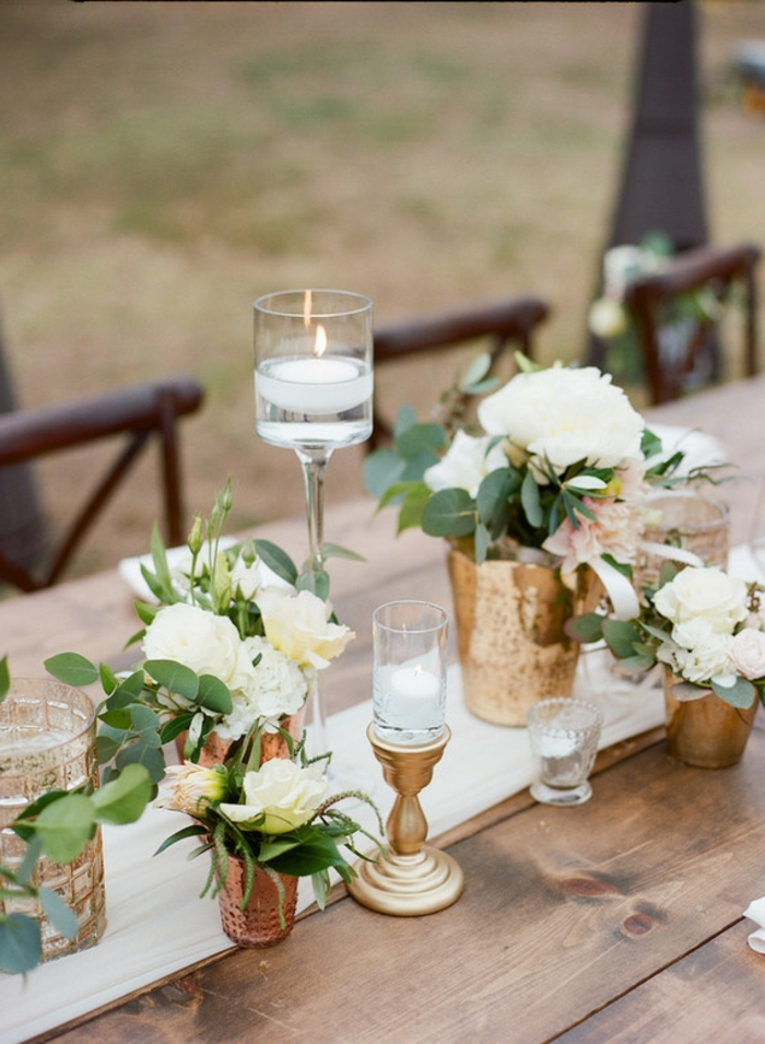 table en bois décorée pour un mariage campagnard, bougeoirs en verre et vases cuivrés