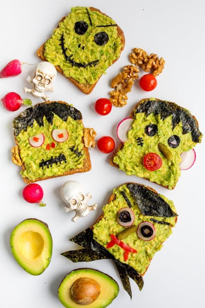 des tartines à l'avocat pour un goûter d'halloween effrayant, décorées avec des olives, radis, cornichons, tomates cerises et feuilles d'algues
