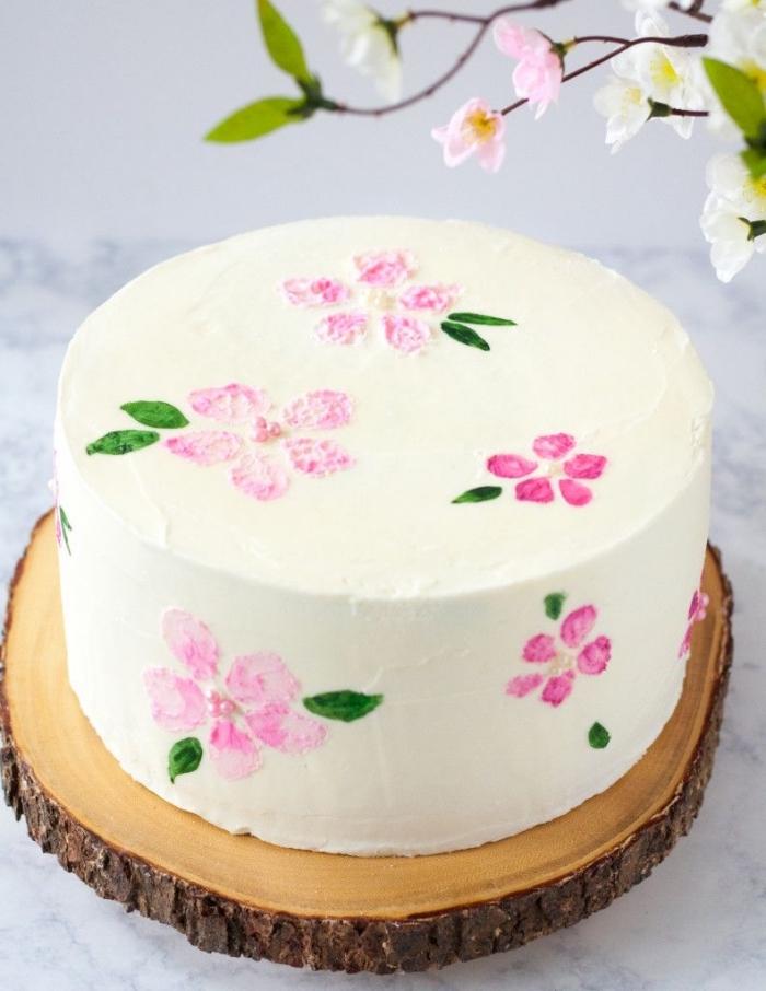 technique facile pour réaliser un dessin gateau anniversaire floral sur un glaçage de crème au beurre, déposé sur un rondin de bois