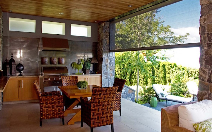 cuisine d'été sur terrasse couverte semi ouverte avec baie ouverte sur jardin