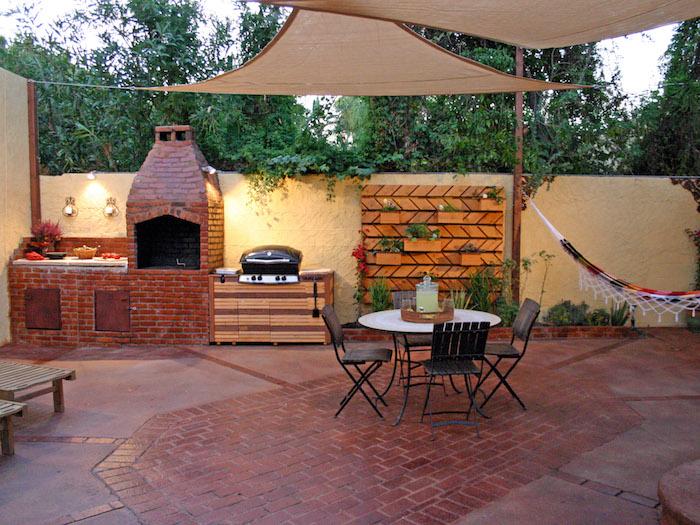 terrasse couverte et coin cuisine d'extérieur avec four en briques et grill en bois
