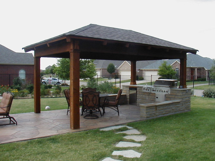 cuisine exterieur en dur pour jardin avec toit en bois et sol en carrelage et coin grill au gaz