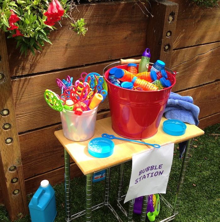 un bar avec outils divers pour faire des bulles de savon, anniversaire 5 ans jeu original en plein air dans le jardin d une maison