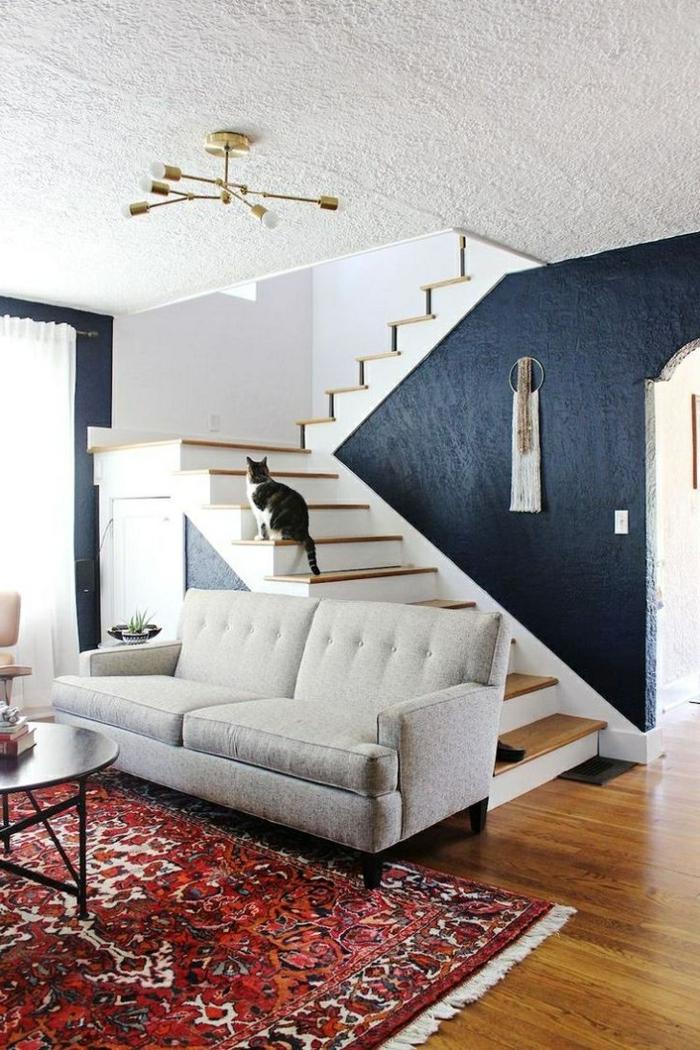 salon espace ouvert près d'un escalier en blanc et bois, sol en bois, sofa gris clair, plafonnier métal doré