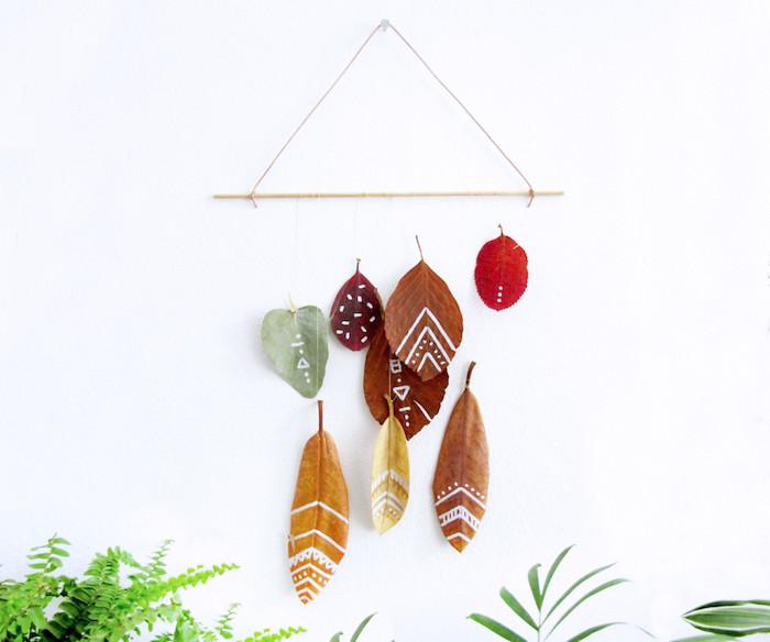 decoration murale feuilles mortes à motifs colorés sur une brindille bois suspendu sur un mur blanc