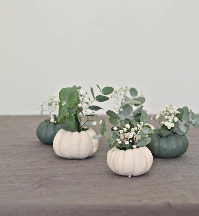 vase de fleur halloween en citrouille creusée avec de petits bouquets de fleurs blanches et feuilles vertes, activités manuelles halloween