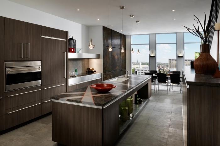 ambiance stylée dans une cuisine ouverte sur le séjour à grandes fenêtres aux murs blancs et meubles foncés