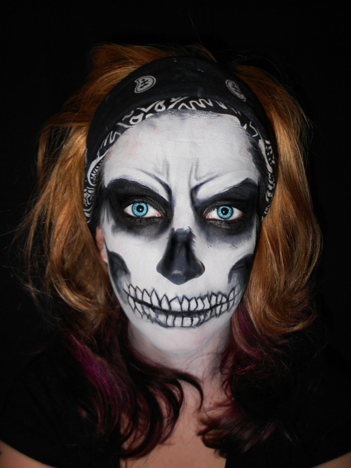 bandeau de cheveux, crâne, cercles autour des yeux, dents, nez noir, rides au front