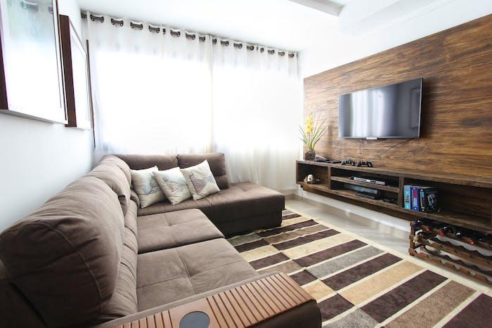 tv en face d'un canapé d angle gris sur tapis gris, marron et beige, comment accrocher un tv au mur habillé de bois