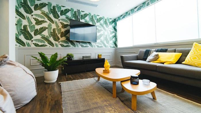 comment bien choisir sa télévision, exemple de deco salon avec support tv orientable à un mur en hauteur sur fond de papier peint exotique, canapé gris, coussins jaunes, tables gigones en bois
