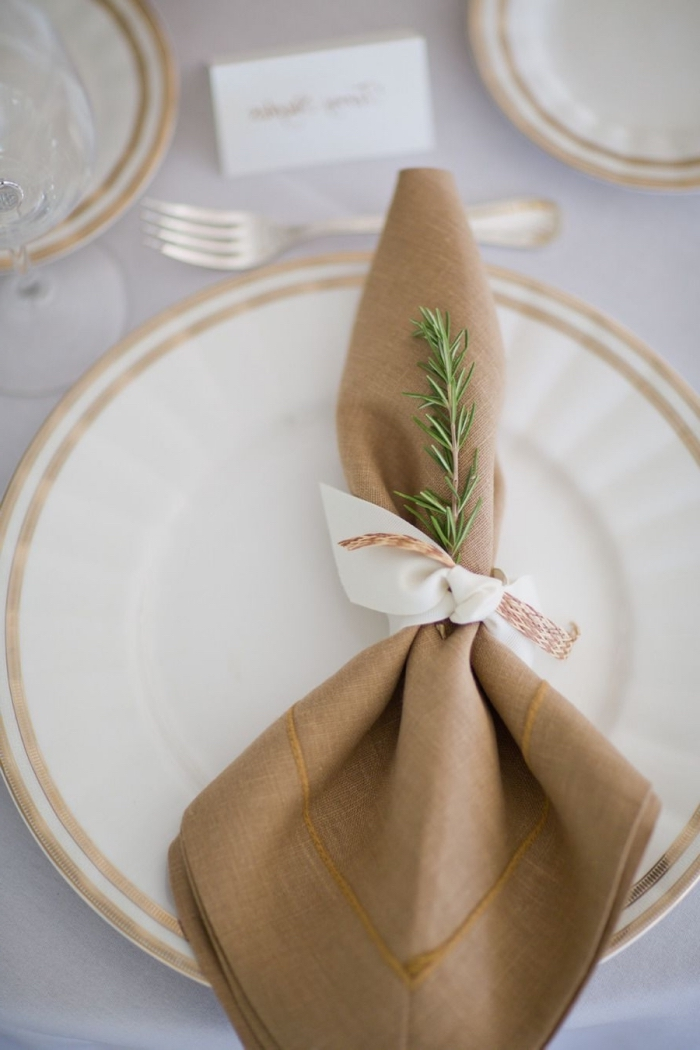 idée décoration de table stylée en blanc et or, exemple de pliage de serviette facile avec ruban blanc et branche de sapin