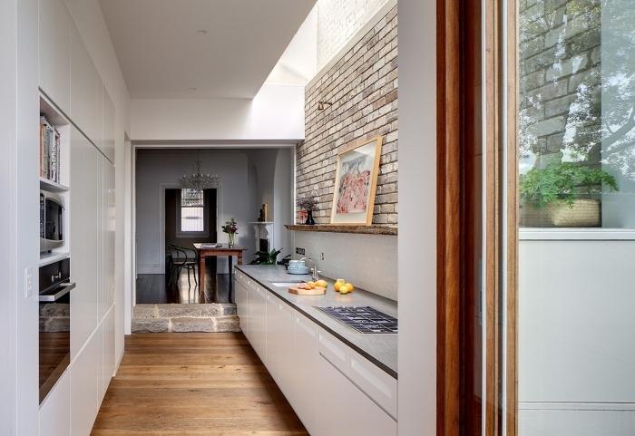 modèle petite cuisine aménagée en parallèle, déco de cuisine blanc et bois avec mur en briques et plancher bois