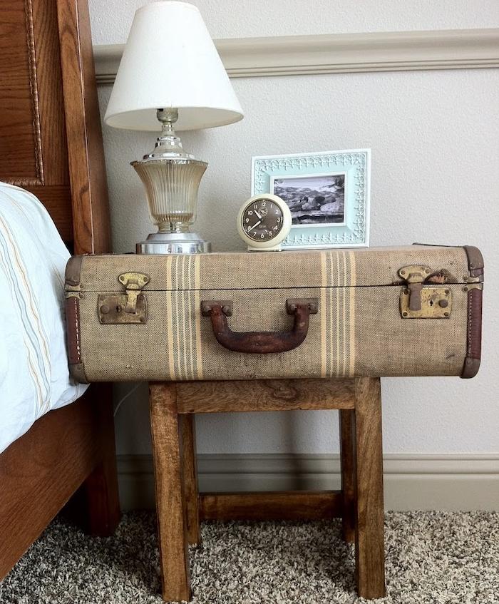 malle vintage sur un tabouret bois en guise de table de nuit dans la chambre à coucher, tapis gris, lit bois style retro chic
