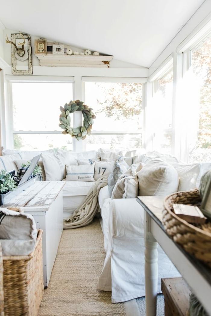 salon déco maison de campagne, toit en pente, grandes fenêtres, couronne de feuilles, panier tressé, plafond blanc en pente, deco maison de campagne cosy