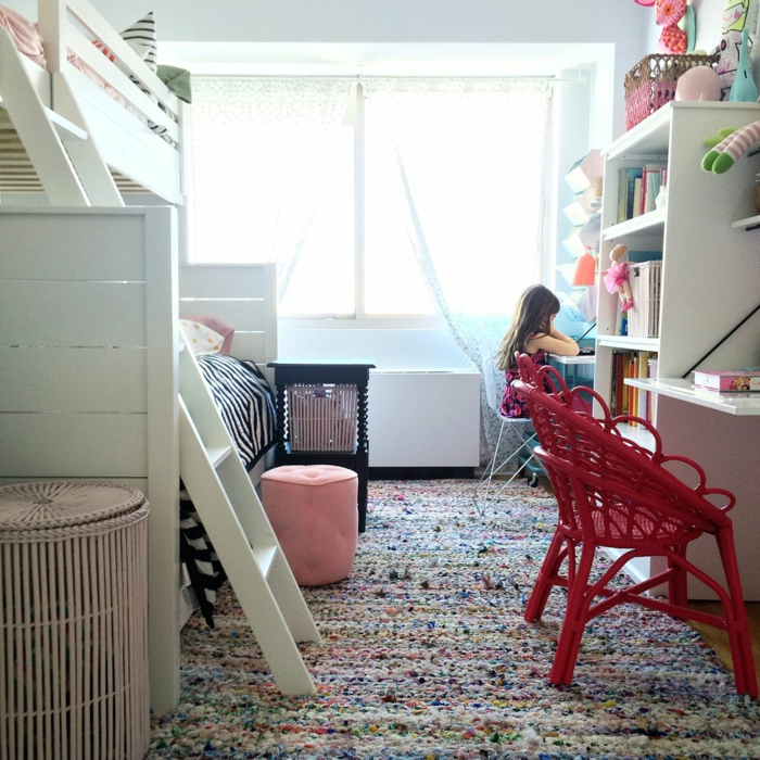 tapis multicolore, lit mezzanine en bois blanc avec échelle, chaises rouges tressées, bibliothèque blanche, panier beige, tabouret rose