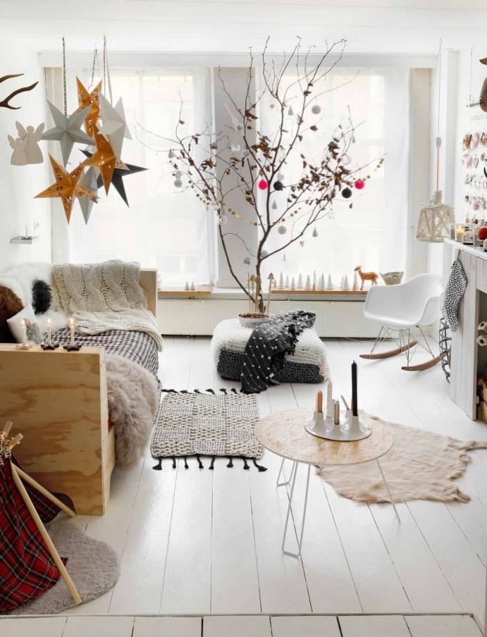 deco cocooning dans un salon blanc de style scandinave qui privilégie les matières et les textiles douillets et chauds, avec un beau arbre de noël décoré pour une touche naturelle dans l'intérieur