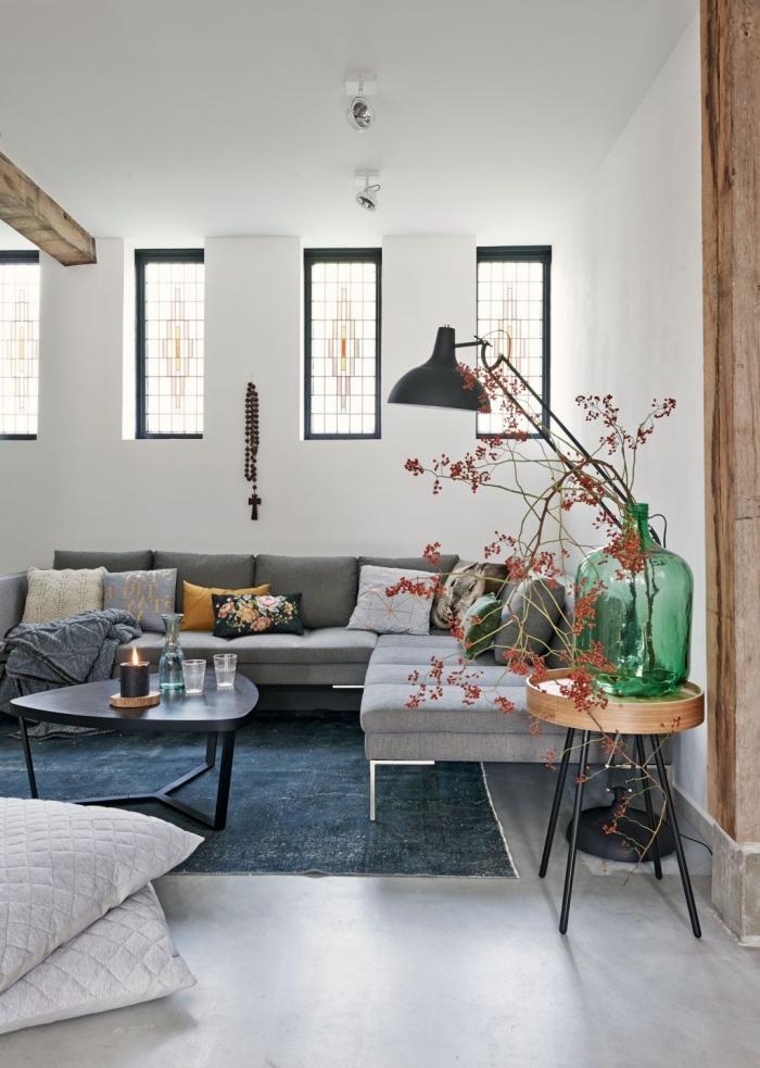 ambiance coсy et accueillant dans un salon de style scandinave avec grand canapé d'angle décoré d'une multitude, salon élégant et cozy aux accents en bois nature