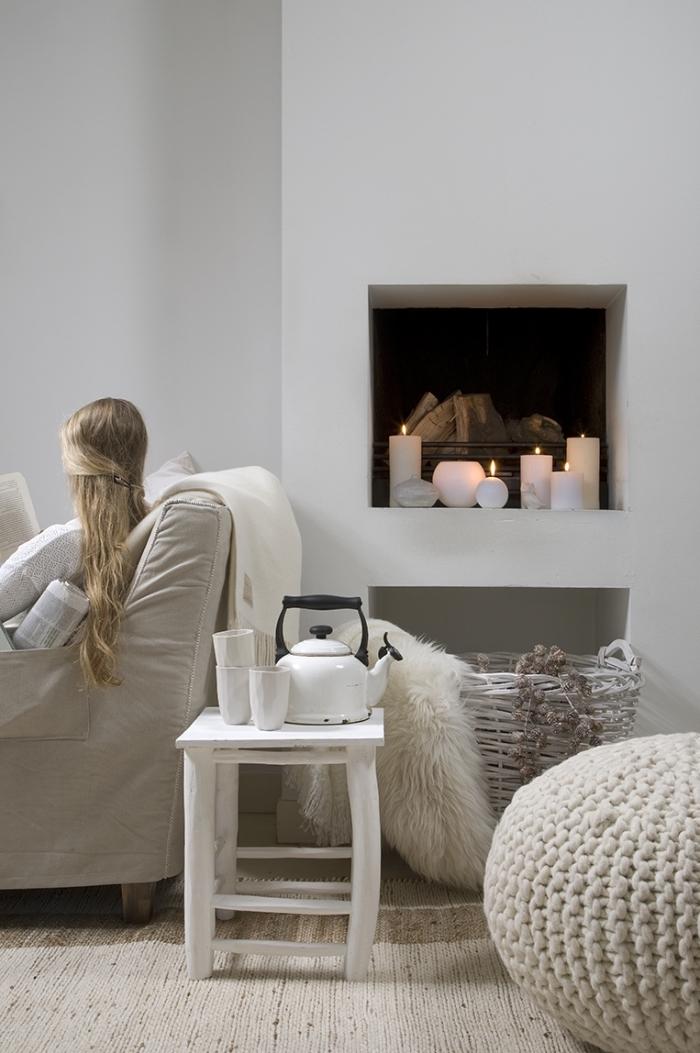 ambiance chaleureux et accueillant dans un salon blanc et épuré, avec coin de lecture cozy, accessoirisé d'un panier de rangement tressé, d'un pouf tricoté