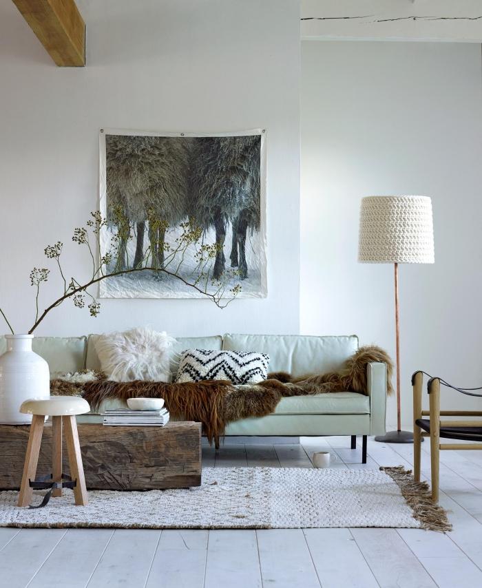 le coussin cozy en fausse fourrure et le jeté transforment le canapé classique en lieu de détente par excellence dans ce salon ethnique chic