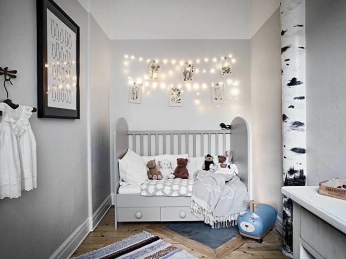 chambre enfant en gris clair, cadre peinture bois foncé, sol rustique, guirlande lumineuse, déco murale tronc de bouleau