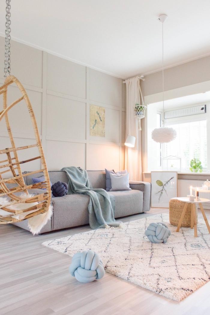 déco cocooning branchée et tout doux avec un tapis cocooning berbère et quelques coussins décoratifs à noeud couleur bleu pastel éparpillés au sol du salon scandinave style hygge