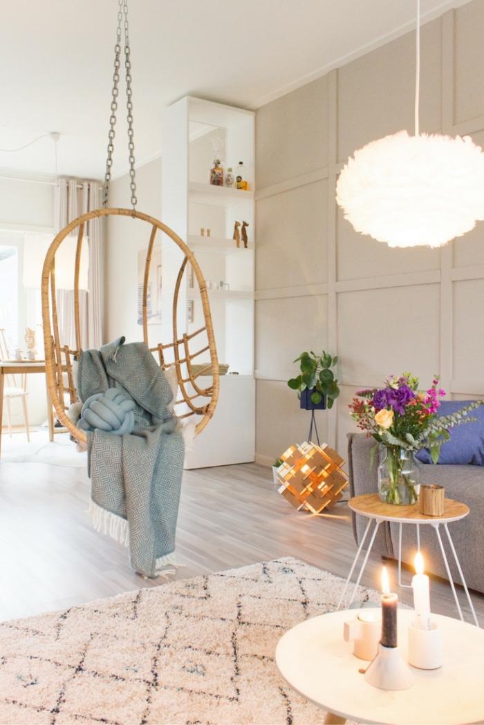 coin relaxante dans le salon avec une balançoire d'intérieur en rotin, un tapis cocooning berbère et un éclairage doux d'ambiance
