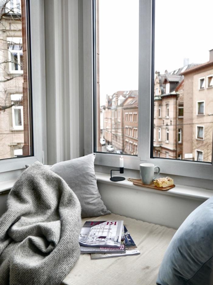 image cocooning avec un petit coin de lecture minimaliste aménagé près de la fenêtre