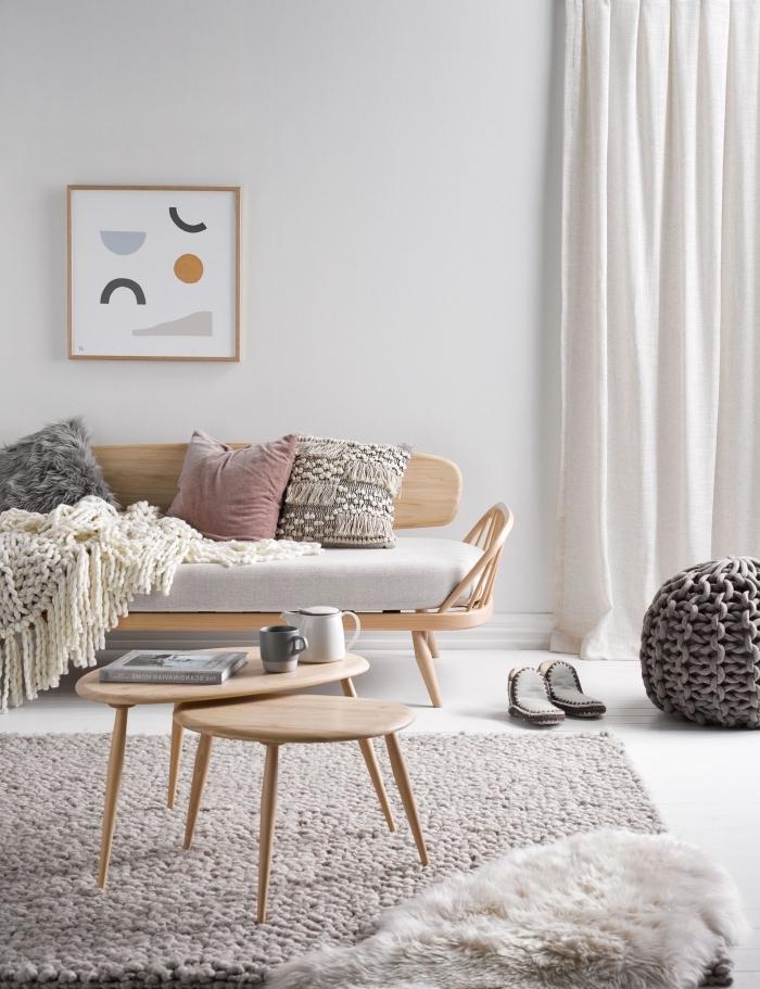 deco salon scandinave vintage aux accents en bois naturel avec un canapé au design unique pimé d'une couverture tricotée et de coussins cocoonings en fausse fourrure et à franges
