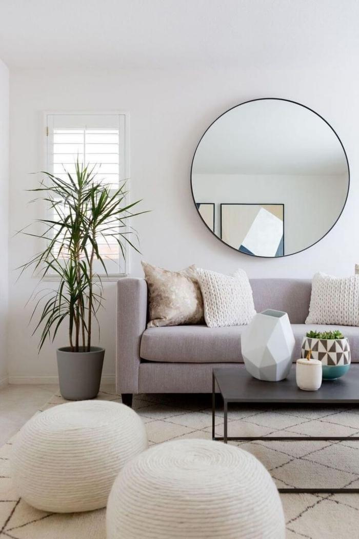 deco sejour en tons neutres et poudrés, avec des poufs en jute, un tapis berbère et un grand miroir rond suspendu en dessus le canapé