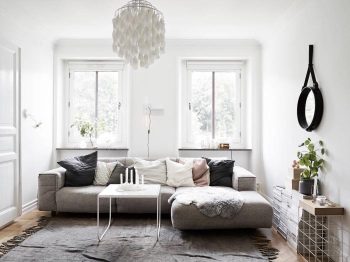 petit salon scandinave monochrome avec un canapé cosy gris recouvert de coussins décoratifs en lin et un tapis frangé