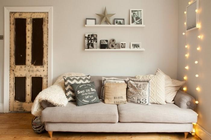 petit coin de détente avec un canapé cosy beige recouvert de coussins décoratifs cocooning de la même tonalité et une déco de guirlande lumineuse suspendue au mur