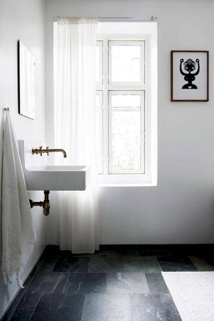 salle de bain minimaliste suedoise avec lavabo carré vintage et plomberie cuivre or retro sur sol carrelage foncé marbré et murs blancs