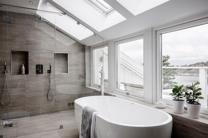 modele de salle de bain mansardée sous les toits lumineuse avec fenetres et velux avec douche italienne carrelée et baignoire ilot ovale