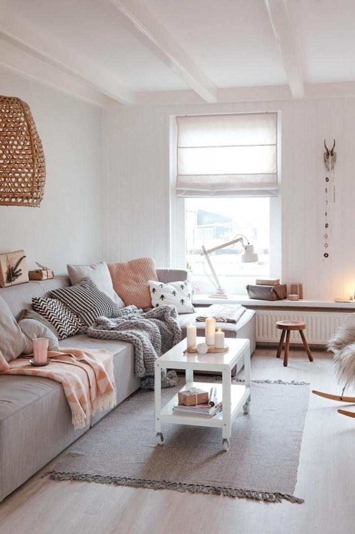 petit salon hygge deco douce et chaleureuse, avec un grand canapé gris recouvert de coussins décoratifs