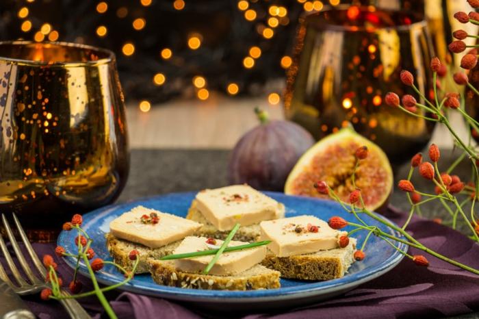 tranches de pain au fromage et aux figues, verres à vin, assiette bleue, fourchette, décoration avec brins d'églantier