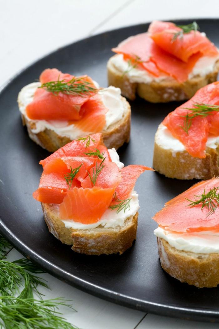 toast apero originale facile, saumon fumé, fromage, brins d'herbes fraîches, tranches de baguette, plateau noir rond