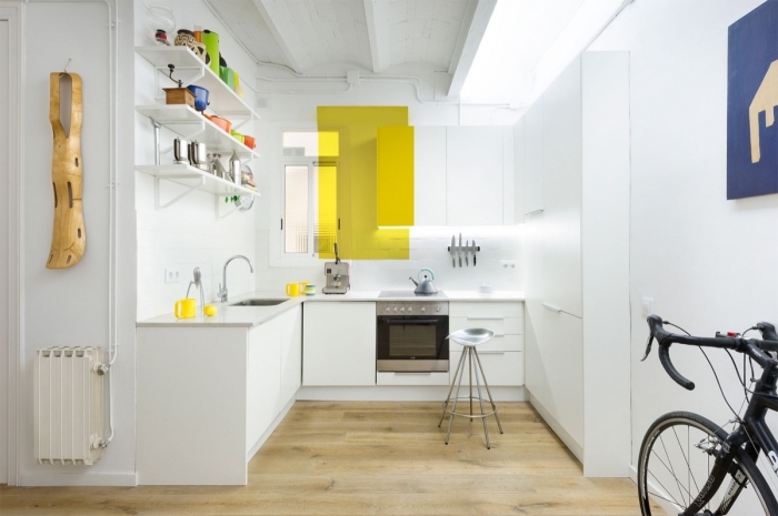 déco de cuisine blanche avec accents en couleur, jolie cuisine en u avec parquet de bois clair et plafond bois peint en blanc