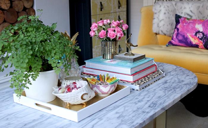 sofa jaune capitonnée, grande table basse marbre, plateau blanc, livres colorés, pot de fleur avec plante, souris en porcelaine