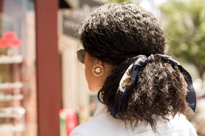 idée comment coiffer les cheveux frisés facilement, exemple de coiffure avec foulard, modèle queue de cheval basse avec accessoire tête