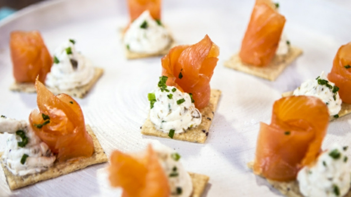 biscuits salés garnis de fromage blanche aux épices et aux herbes, filet de saumon enroulé