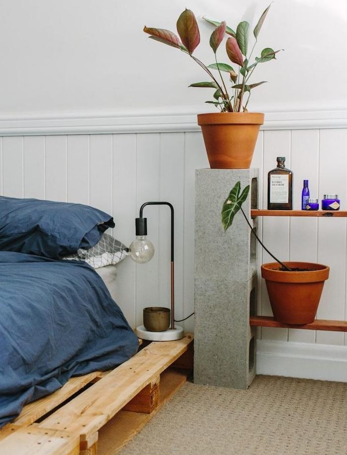 blocks de béton et planches de bois pour creer les rayons d une table basse décorée de plantes vertes et autres objets deco, sommier en palette linge de lit bleu marine