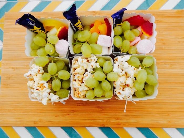 boîte pop corn remplie de pop corn, raisins, murshmallow guimauve, gélifiés et de petits dessets sucrés, idée repas simple