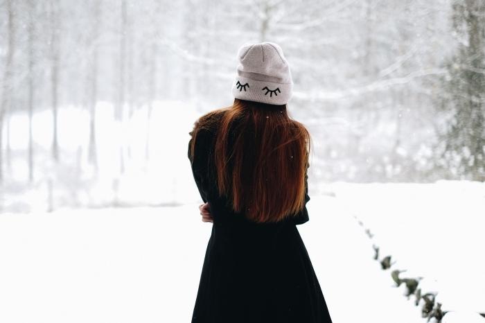 idée image de noel gratuite a telecharger, photo de jeune fille habillée en vêtements chauds pour hiver devant un paysage hiver