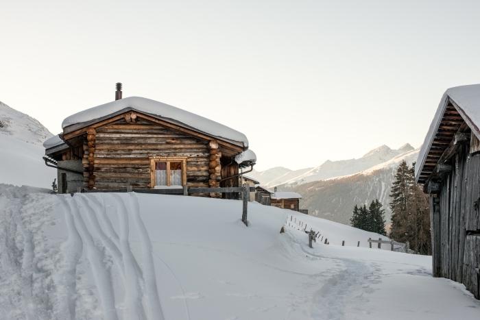 exemple de fond d écran hiver avec des maisons de bois sur colins, vue vers les sommets enneigés et lever du soleil