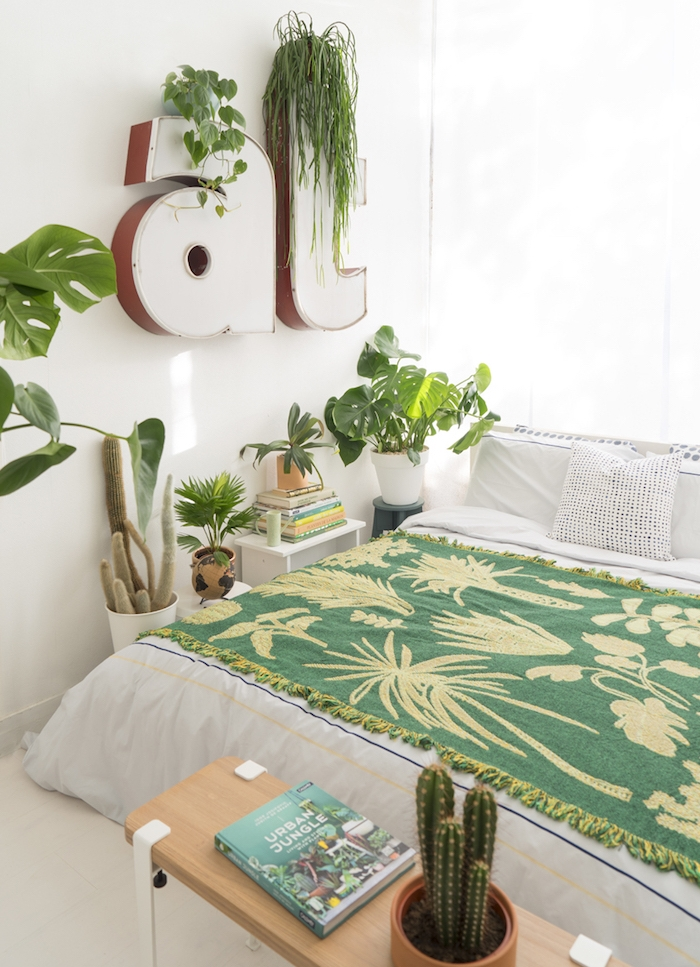 deco chambre adulte moderne en linge de lit blanc, et couverture de lit verte, deco lettres blanches avec accents verts et autres pots de fleurs avec plantes exotiques