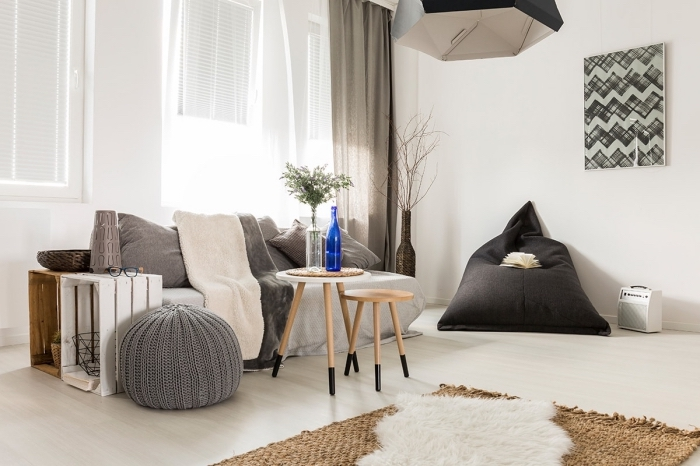 deco salon scandinave en tons neutres et aux accents bois avec un petit canapé cocooning à côté duquel sont rangés des caisses en bois récupérés