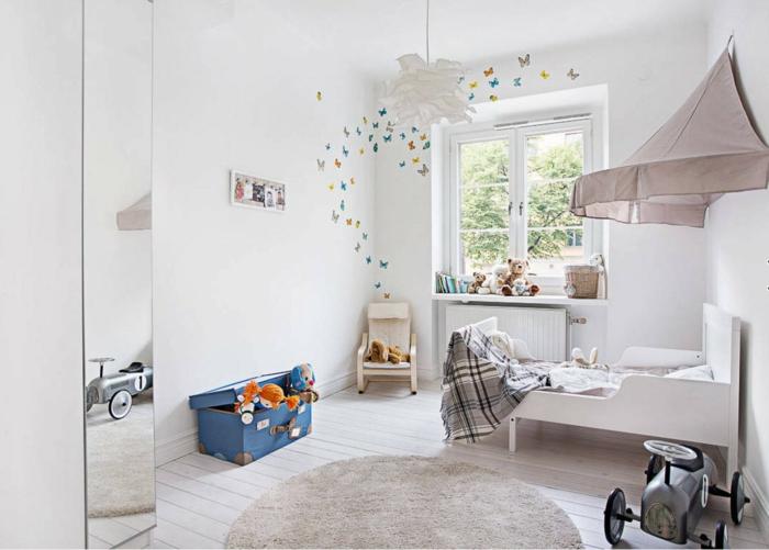 aménagement de petite chambre enfant, tapis gris clair, lit et tête de lit originale, plafonnier blanc, grand miroir, coffre à jouets valise vintage